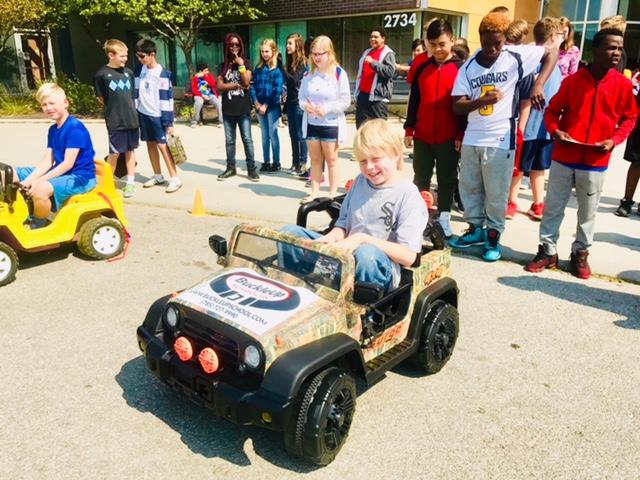 Children driving BuckleUp big wheel cars