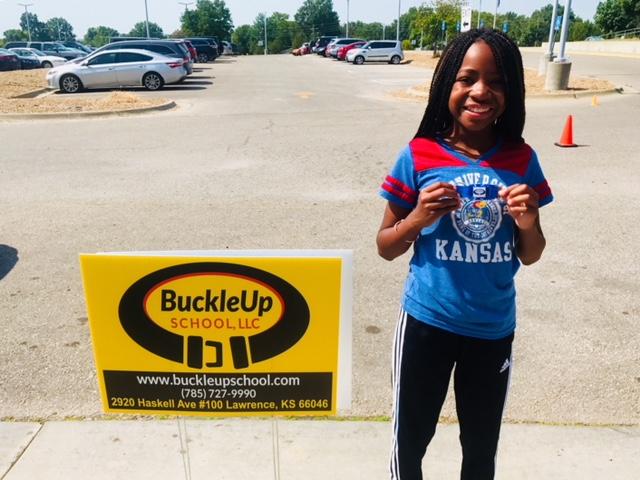 Child with BuckleUp Schools sign